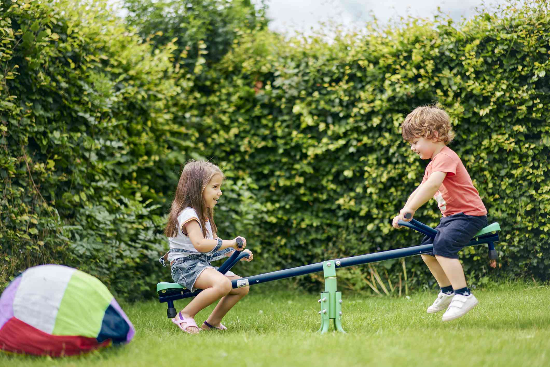 Girl and boy on toy seesaw in garden