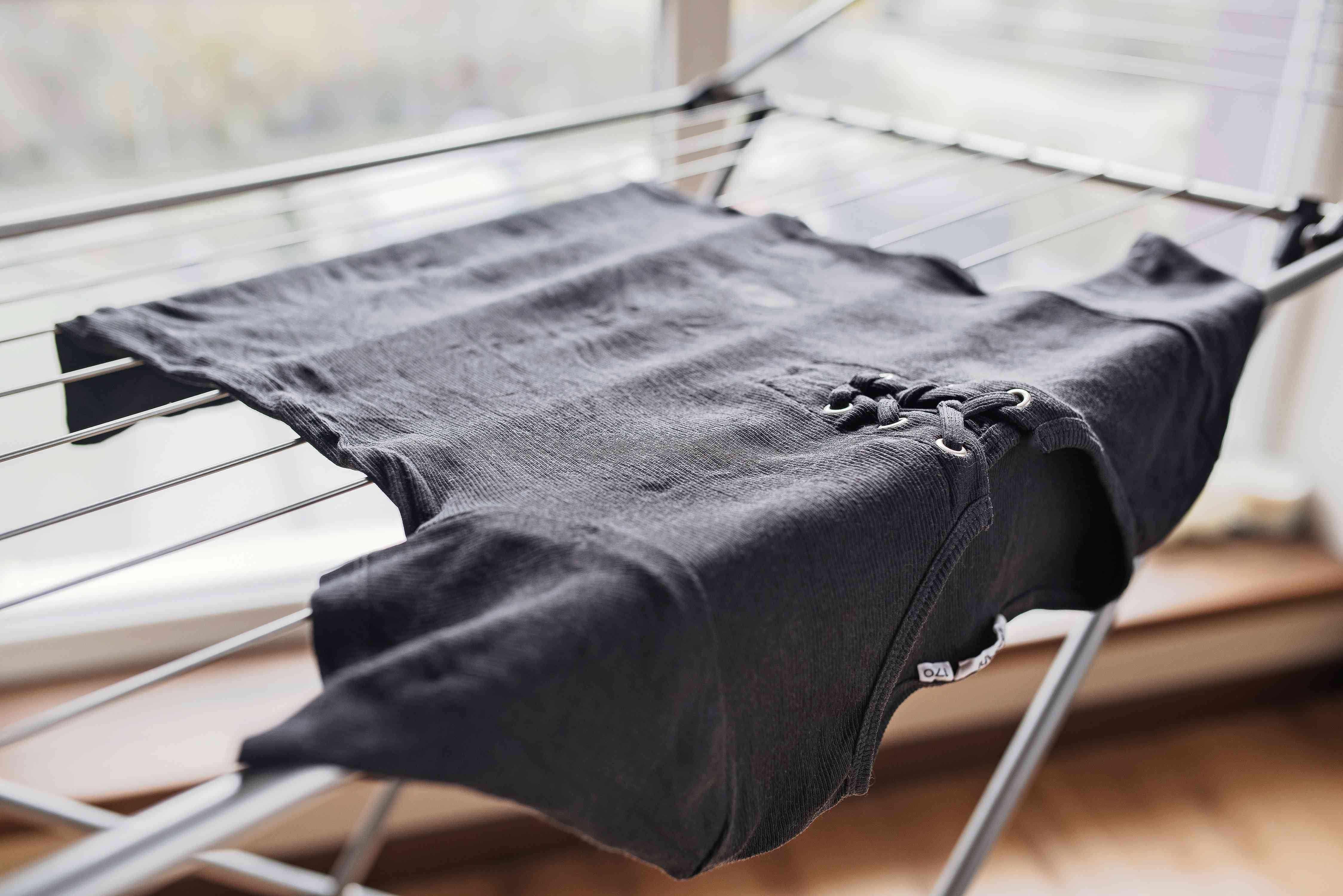 Black shirt with correction fluid stain air drying on rack