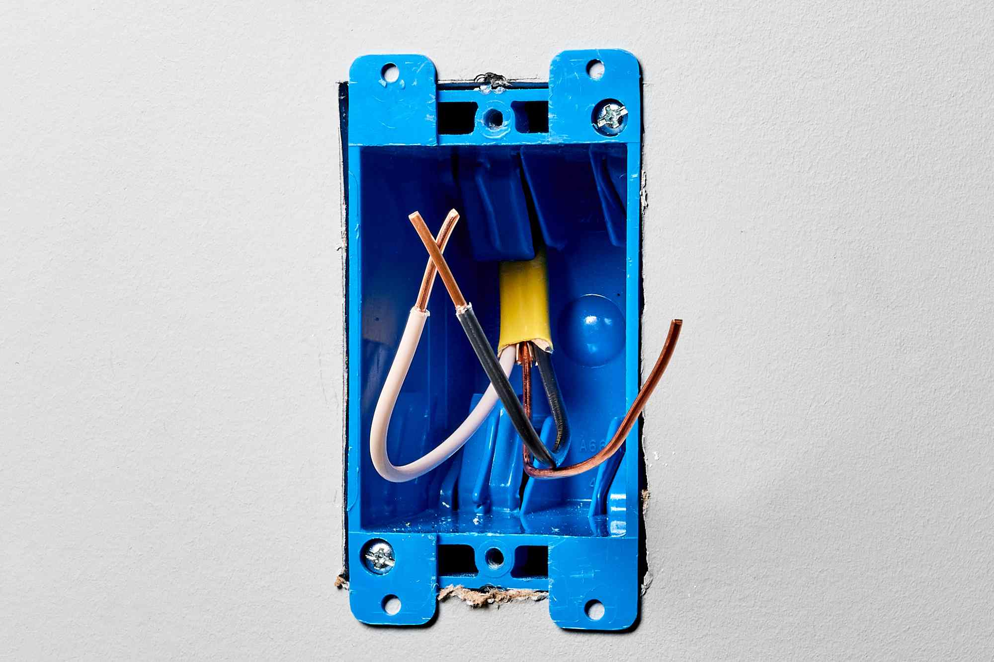 Exposed blue electrical switch box with short circuit wires
