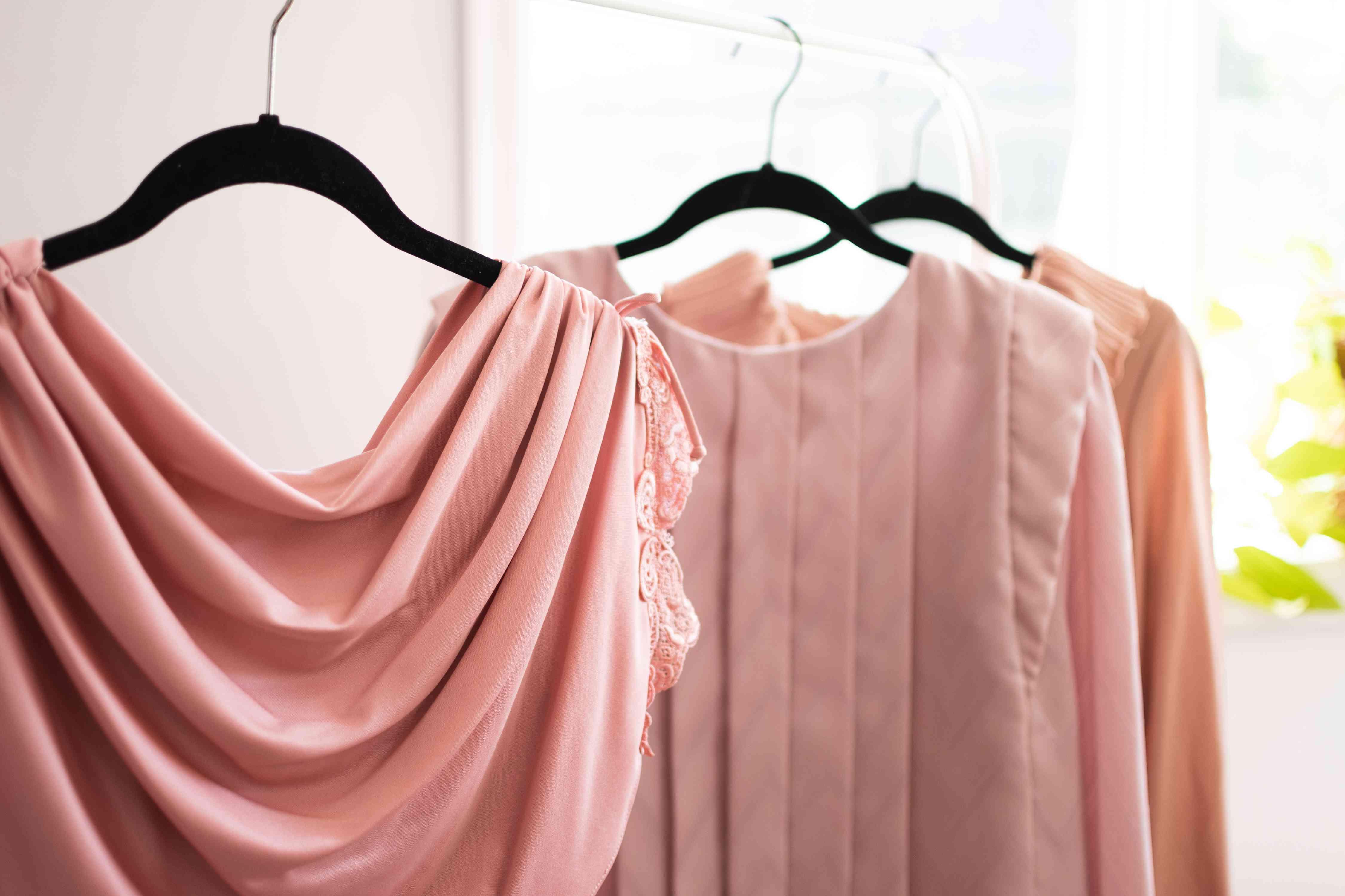 Pink acetate blouses hanging on black hangers