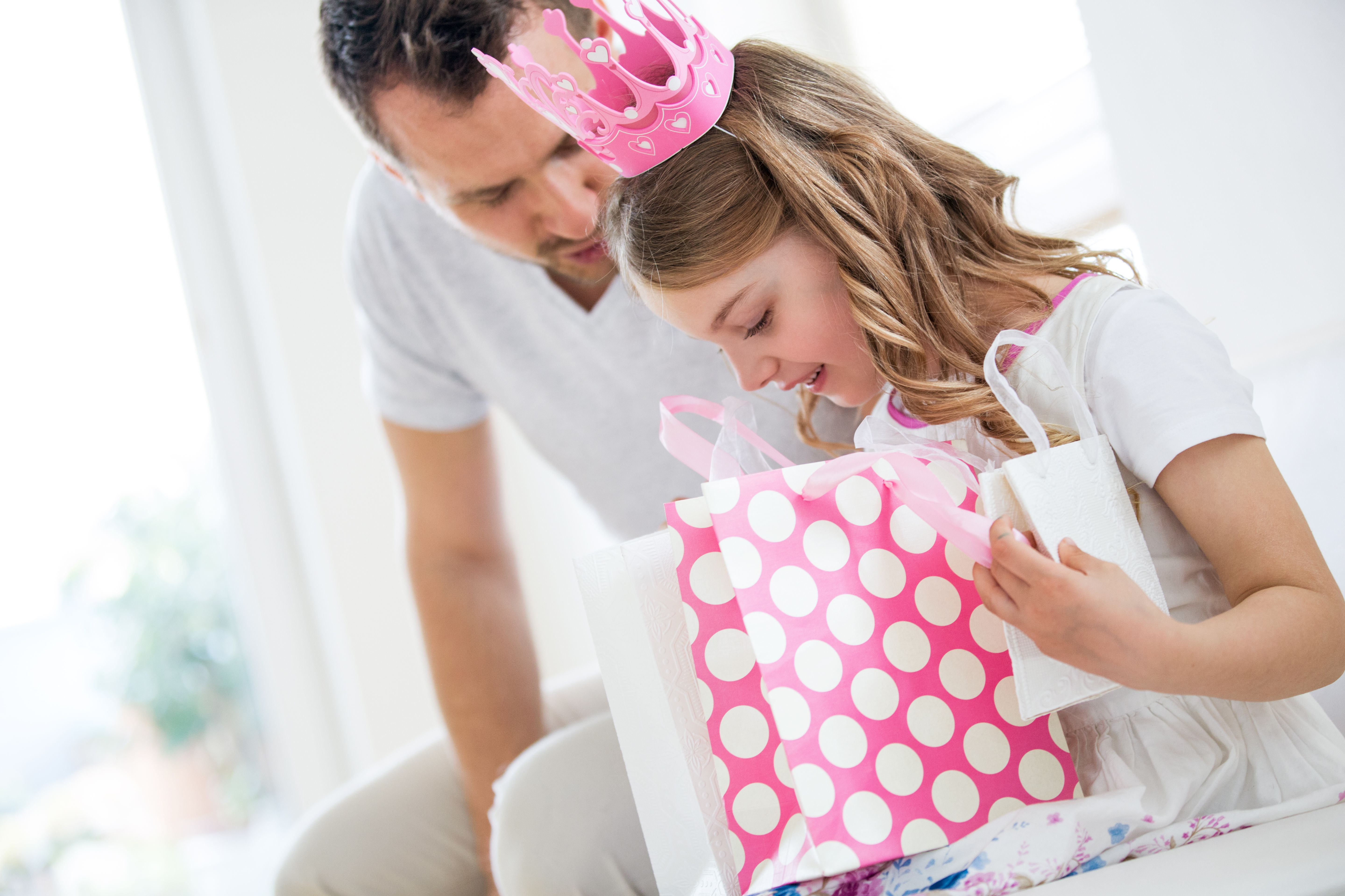 Girl wearing pink crown holding gift bags, father watching