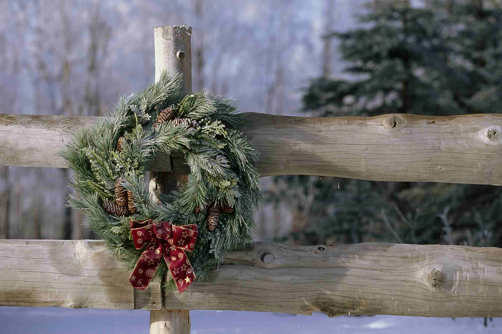 Wooden fence decorated with a Christmas wreath.