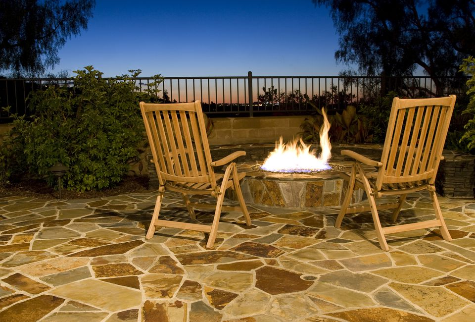 Two chairs around a fire pit on a flagstone patio.