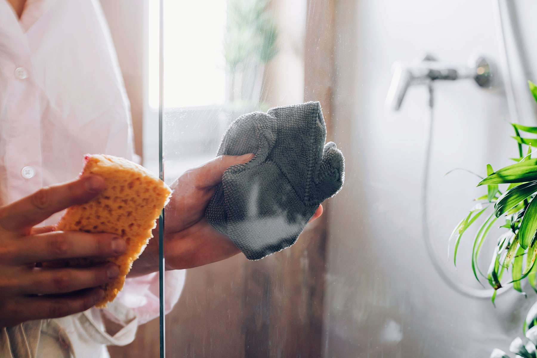Gray microfiber cloth drying glass shower door after spraying Ammonia and water solution