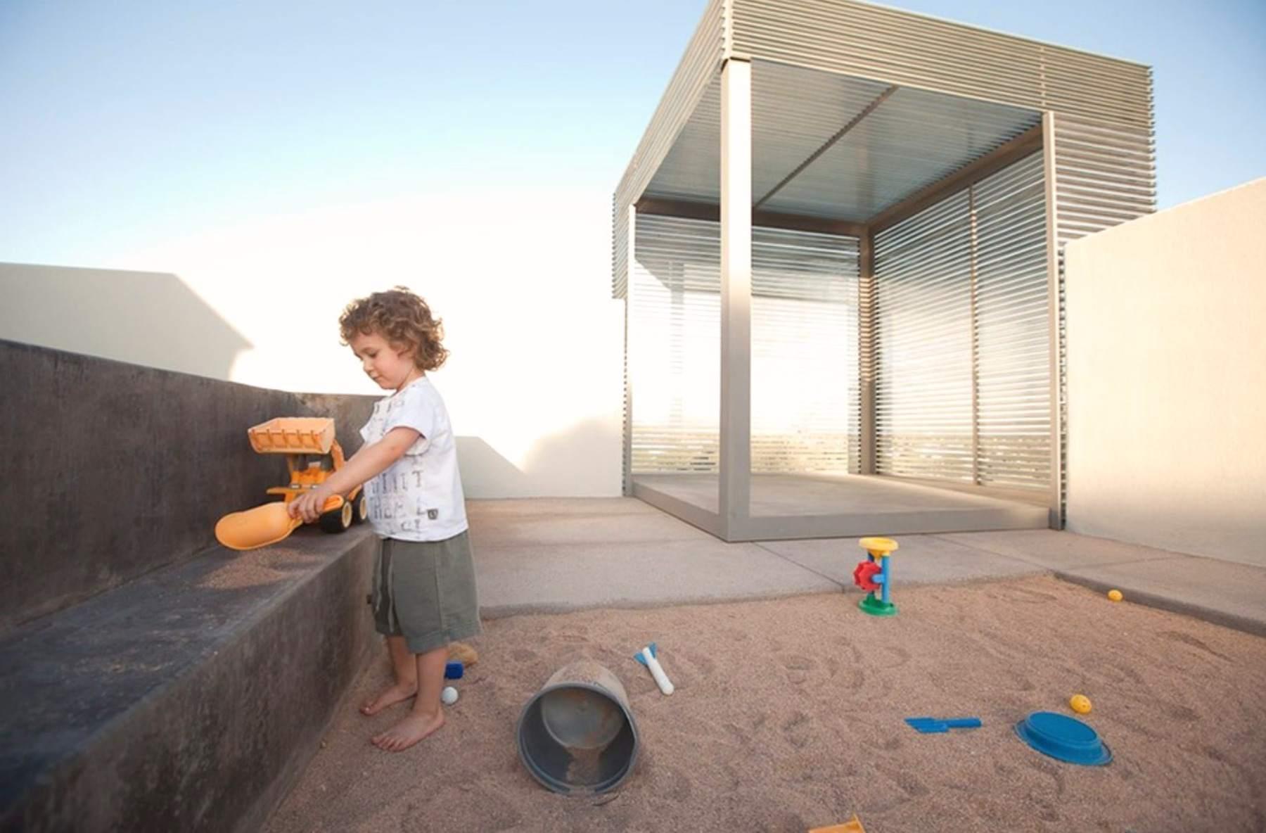 niño jugando en cajón de arena