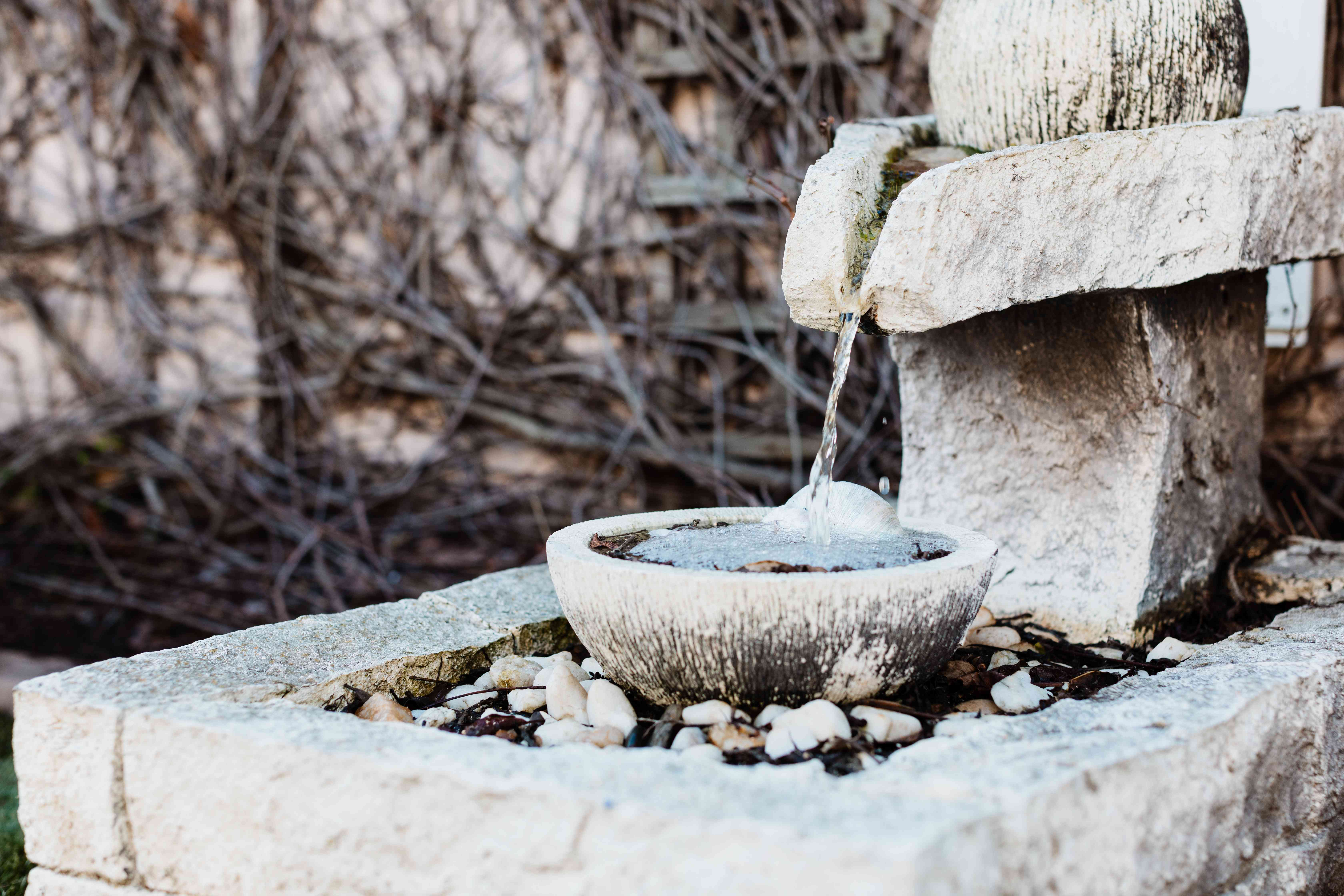 Decorative water fountain with treated water to prevent mosquitos