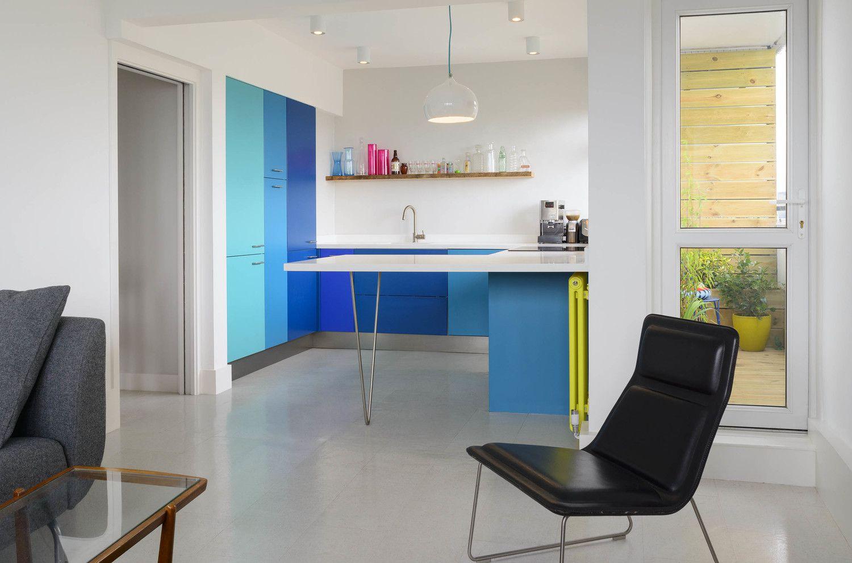 Cocina con gabinetes azules y encimera blanca con silla negra.