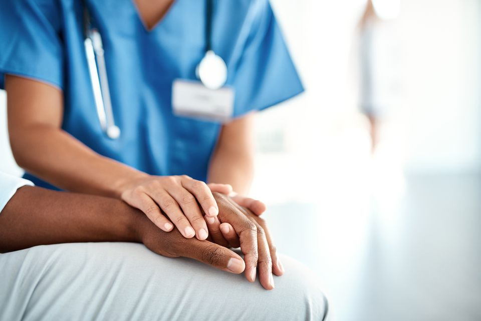 Una enfermera sosteniendo la mano de un paciente