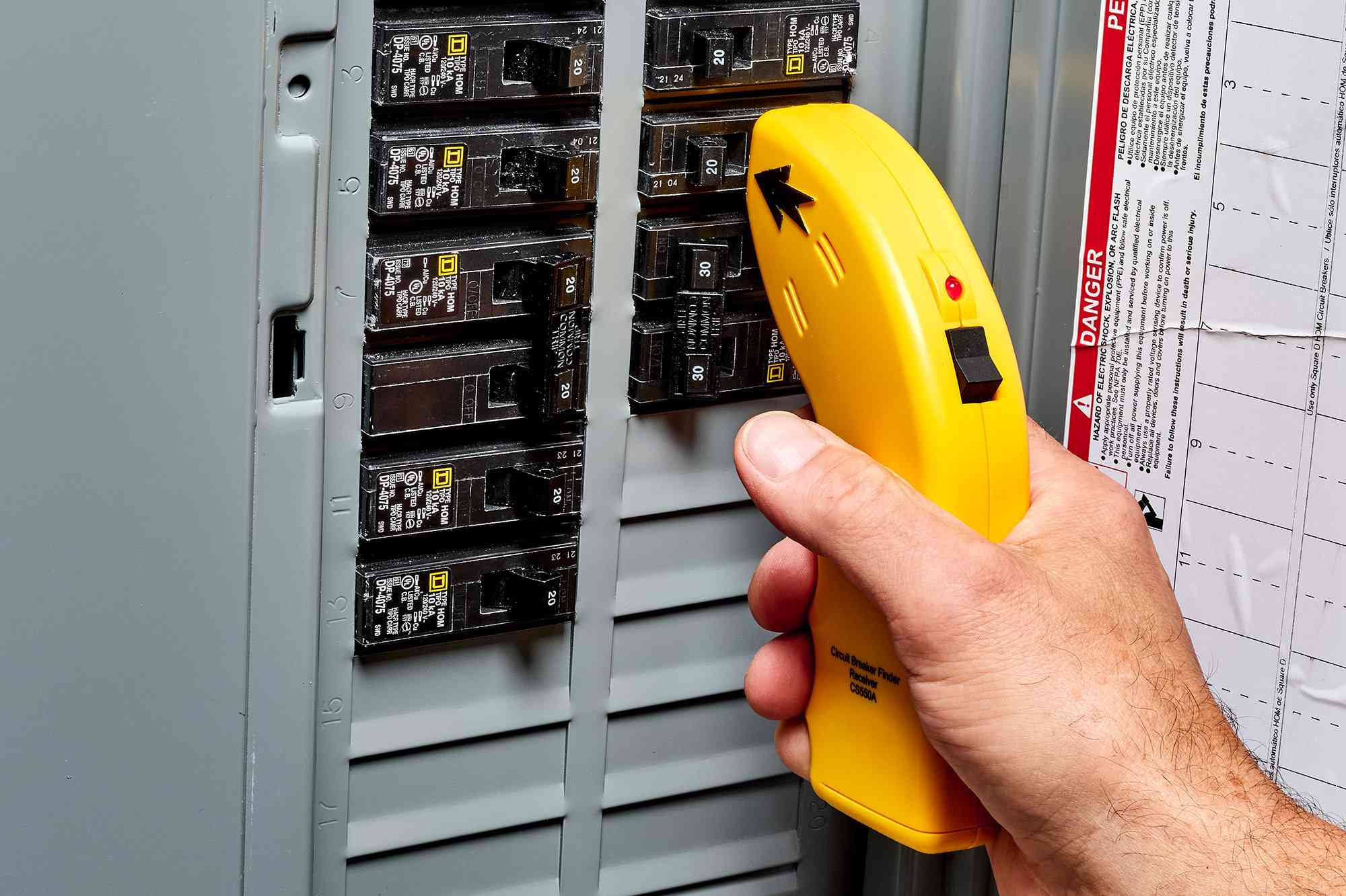 Circuit breaker box opened with receiver's sensor tip pointed to matching circuit breakers