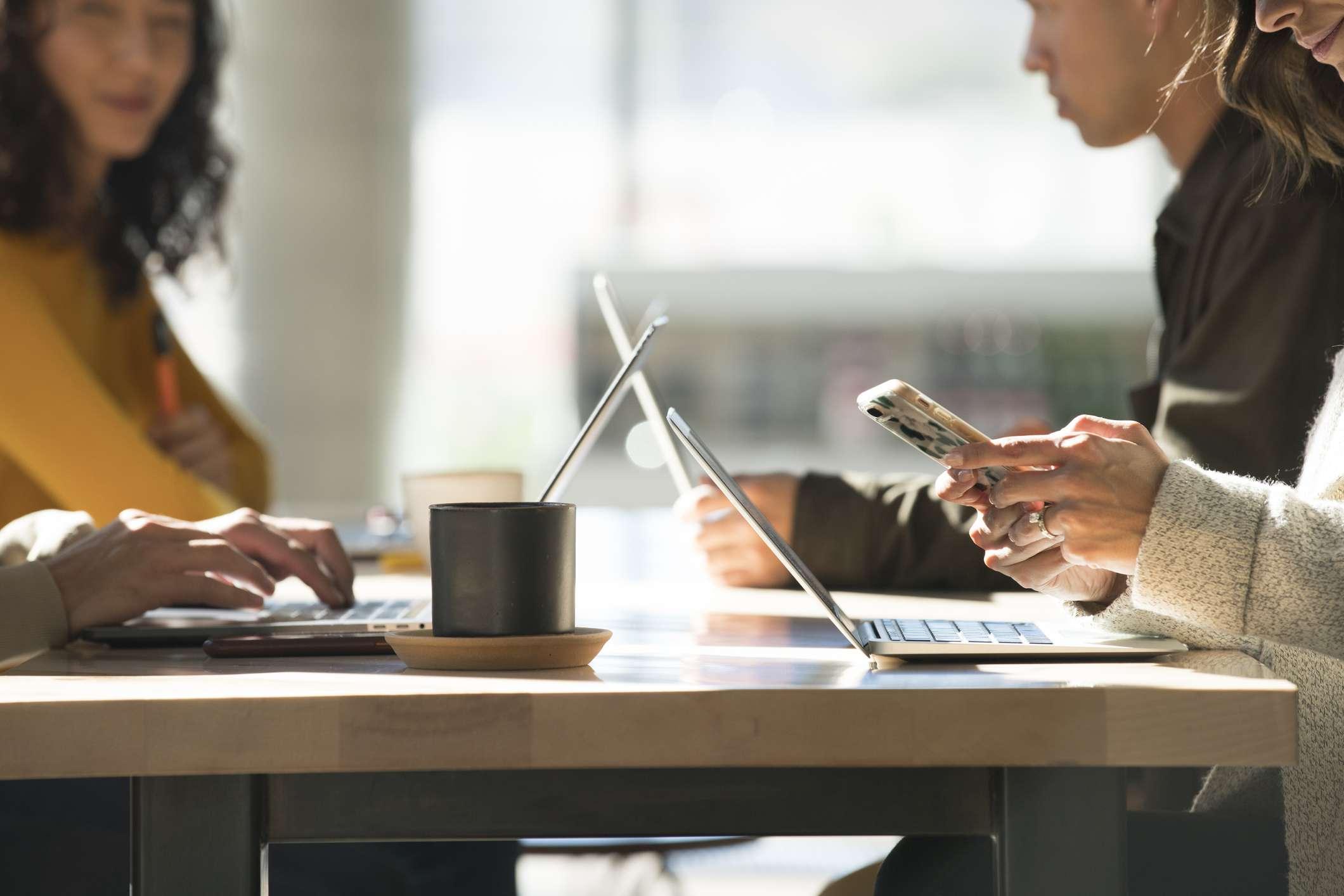 Cerca de jóvenes que trabajan en computadoras portátiles en un espacio moderno