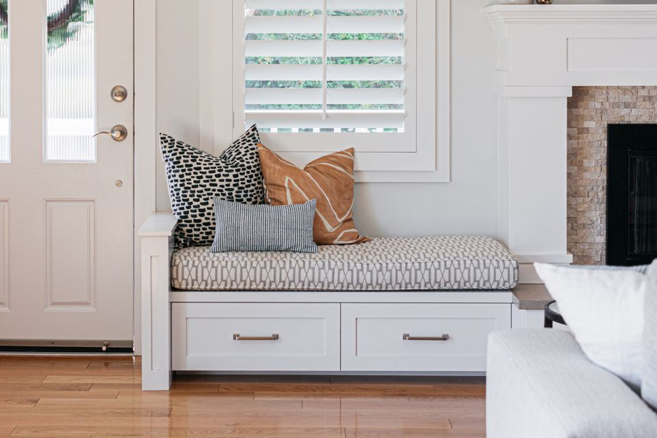 Window seat with white drawers and multiple patterned pillows and cushion