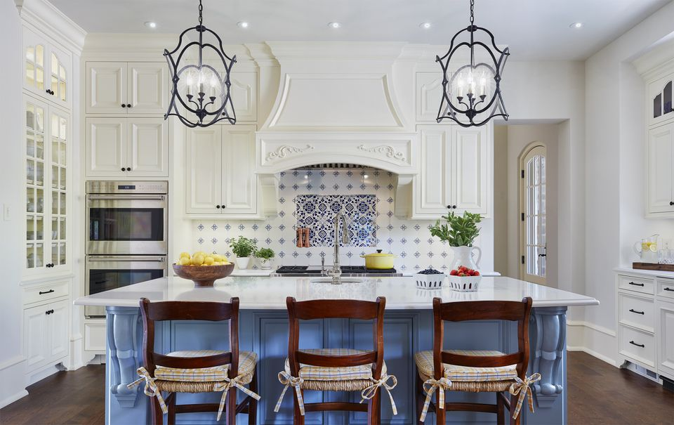 Crisp French country kitchen with blue cabinets, three chairs, and hanging pendant lights.