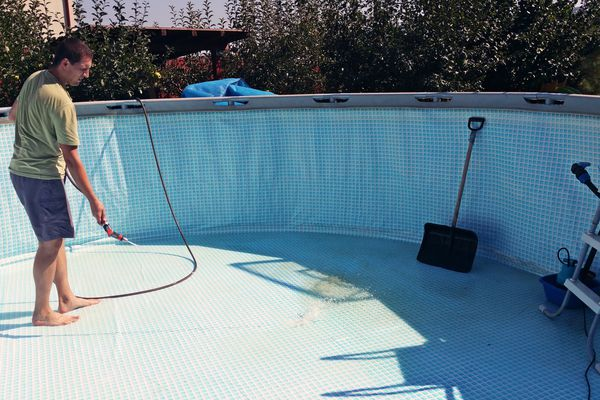 man cleaning above-ground pool