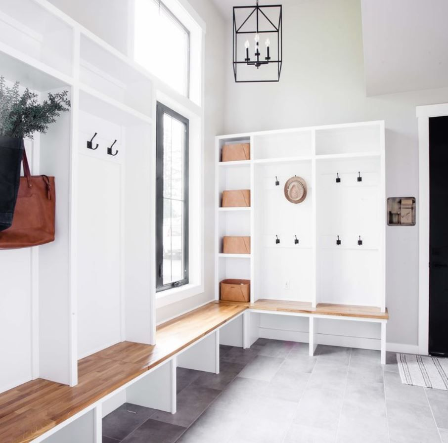 Large mudroom with lots of natural light and white and wood farmhouse features.