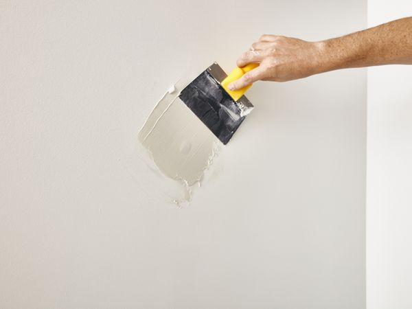 person repairing hole in drywall