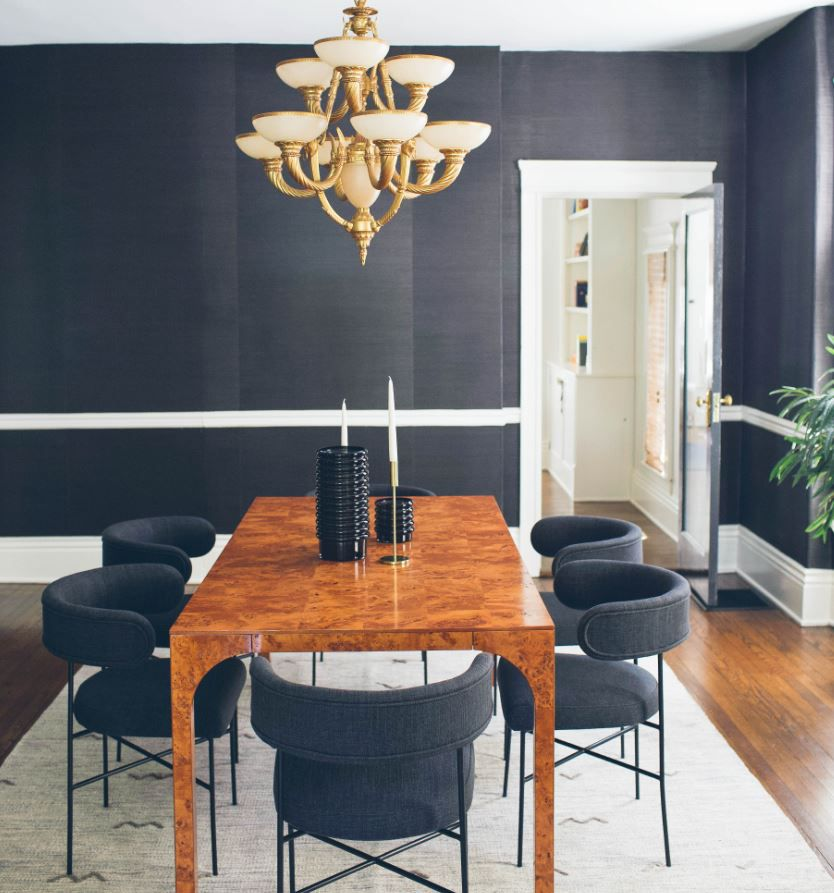 Dining room with black wallpapered walls and brass chandelier.