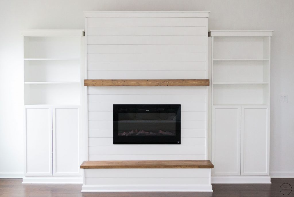 A fireplace with built-in bookshelves