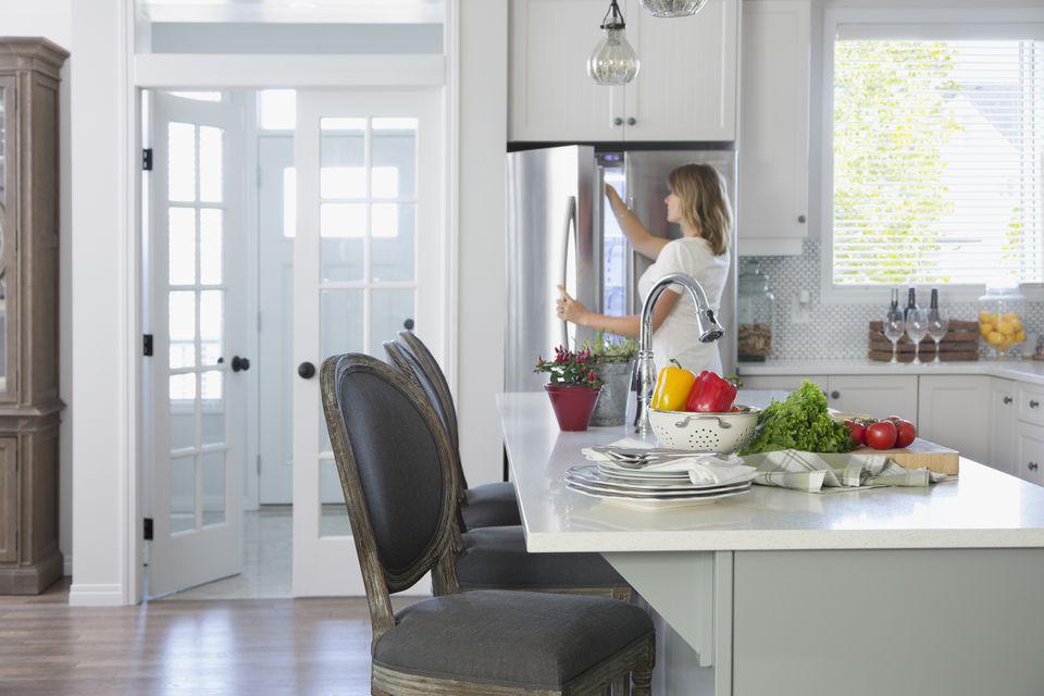 Mujer abriendo un refrigerador en la cocina.