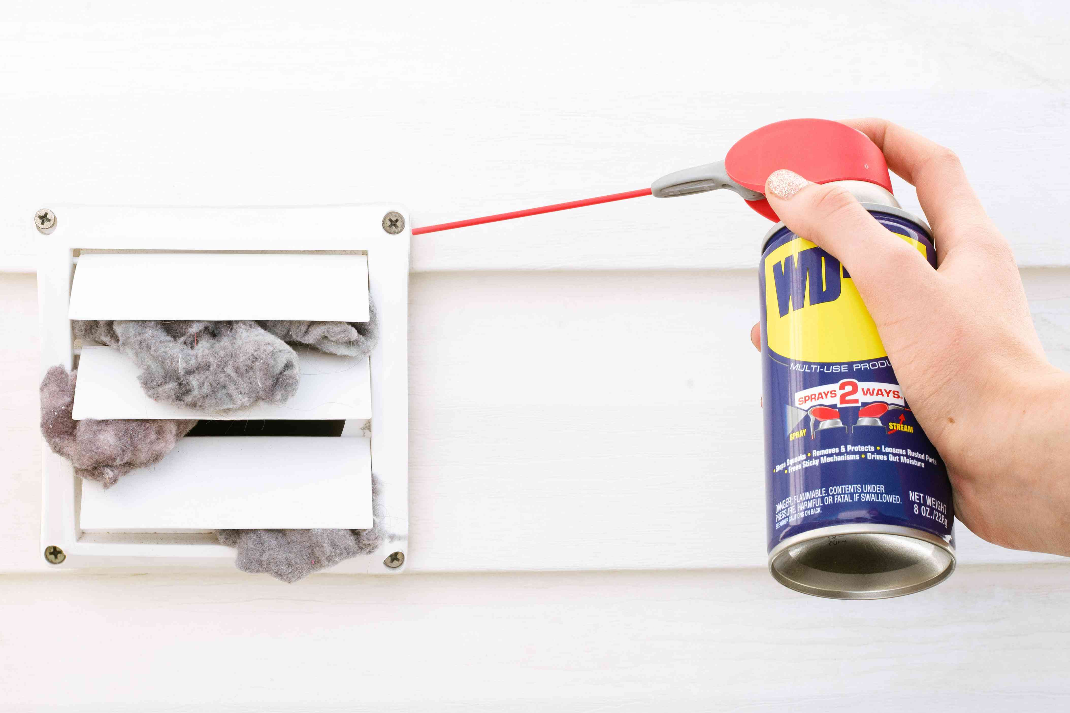 Lubricant added to outside dryer vents with handheld WD40 can