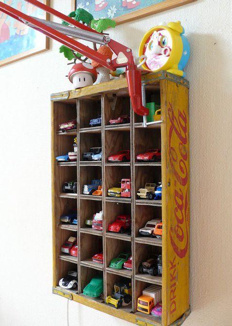 Caja de botellas vintage reutilizada como estante de almacenamiento de automóviles de juguete