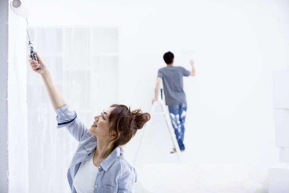 Young couple painting new home