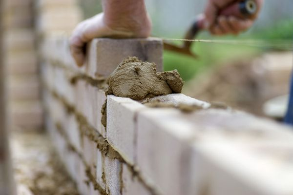 The experienced hands of a bricklayer as he lays the next course of bricks