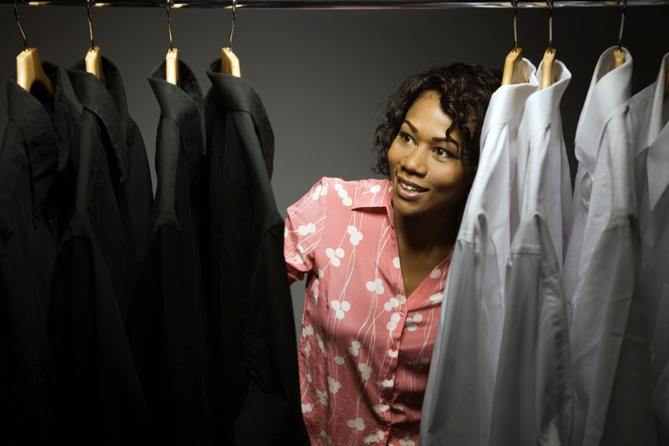 Woman looking at shirts and suits hanging in a closet