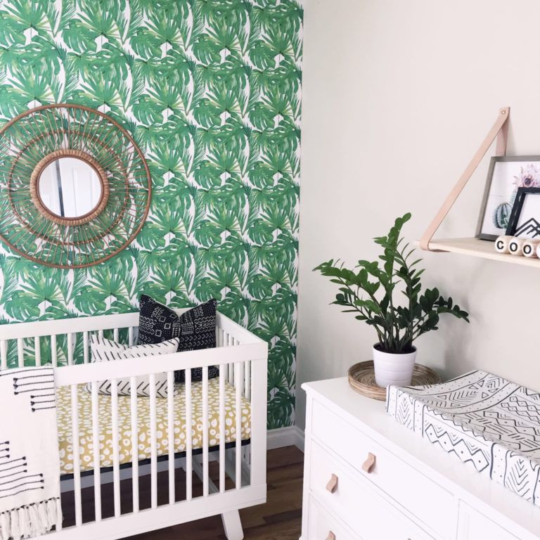 Nursery with green, tropical-print accent wall and yellow accents