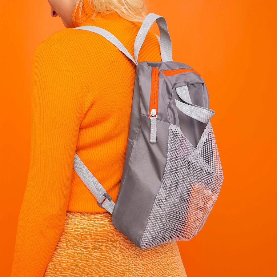 girl wearing orange outfit against orange backdrop wearing IKEA backpack