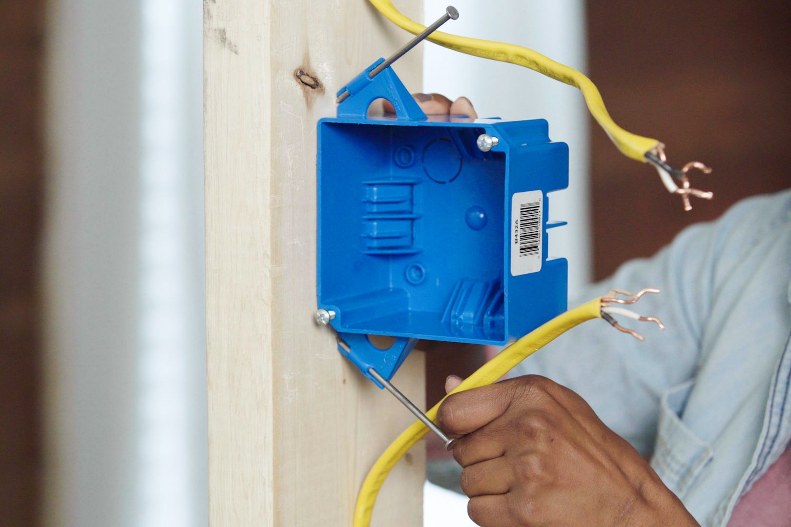 Blue electrical junction box mounted to wooden support with yellow wires loosened for room