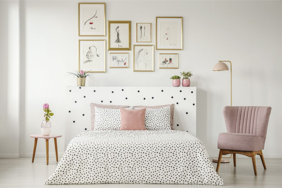 Framed poster gallery above bed with polka dot headboard.