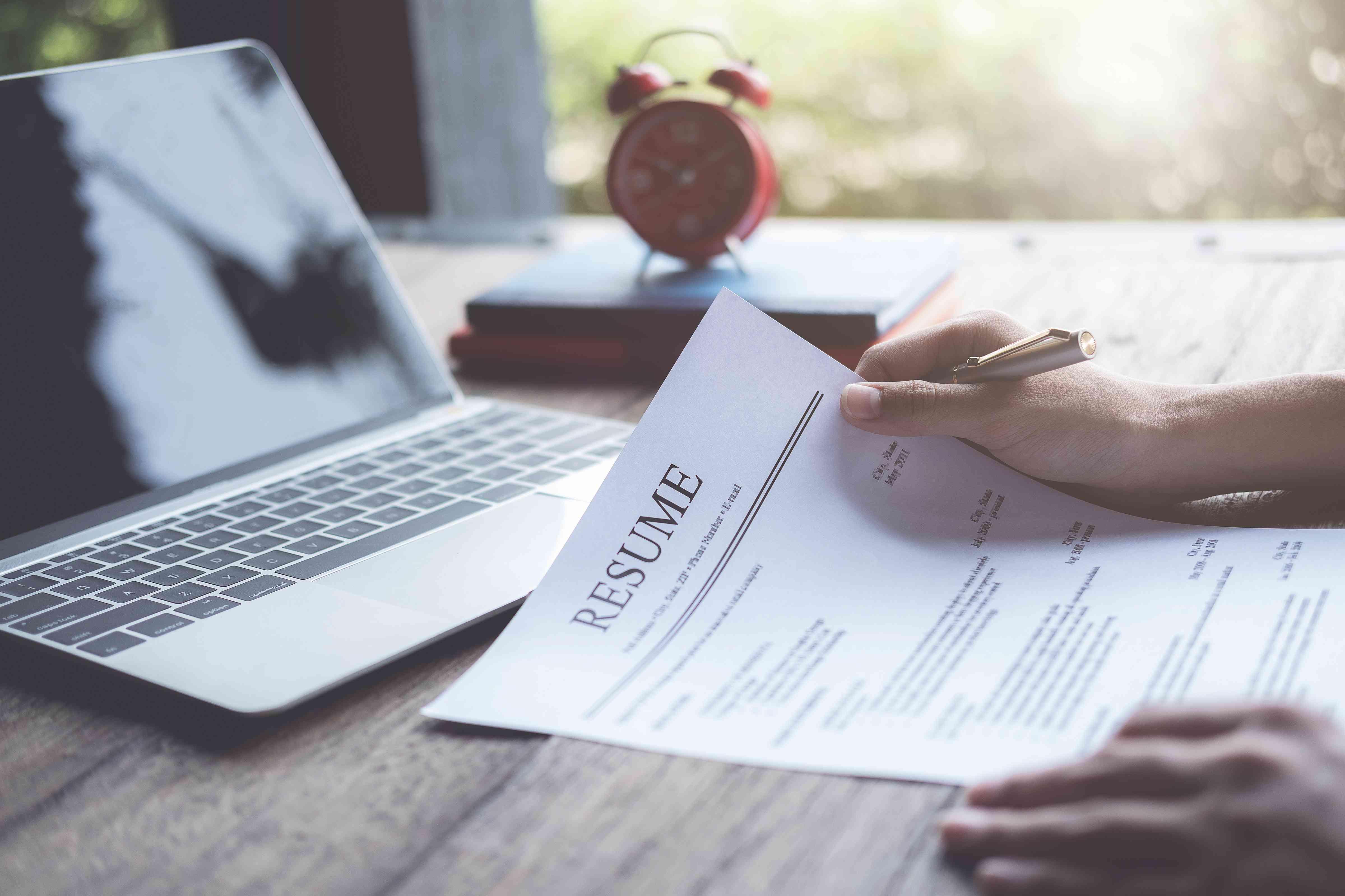 El hombre de negocios revisa su solicitud de currículum en el escritorio, la computadora portátil, el buscador de trabajo