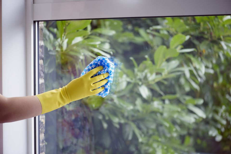 Woman wearing yellow washing up glove to use rag to clean window