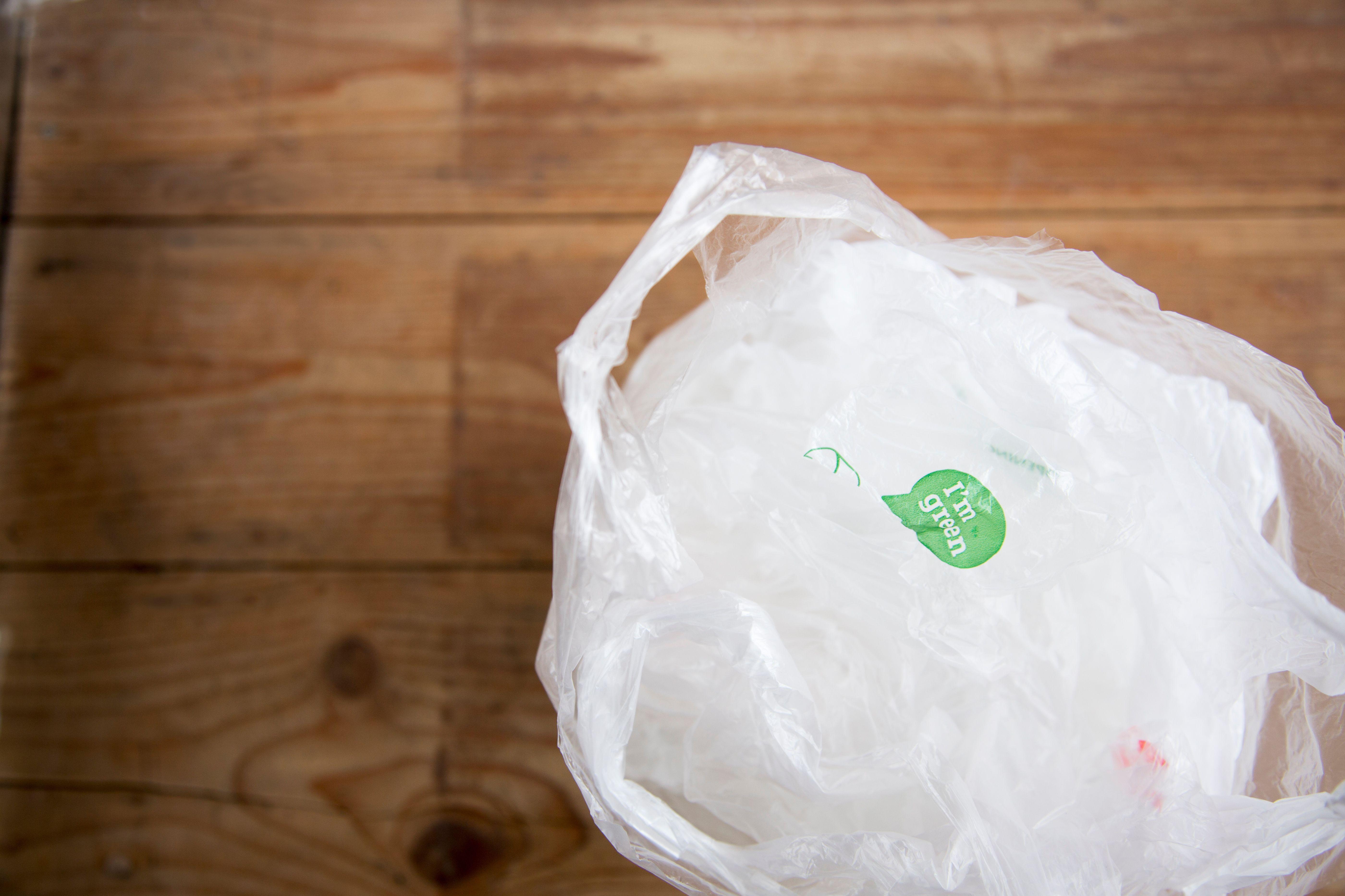 Bolsas de plástico reciclables en el piso de madera