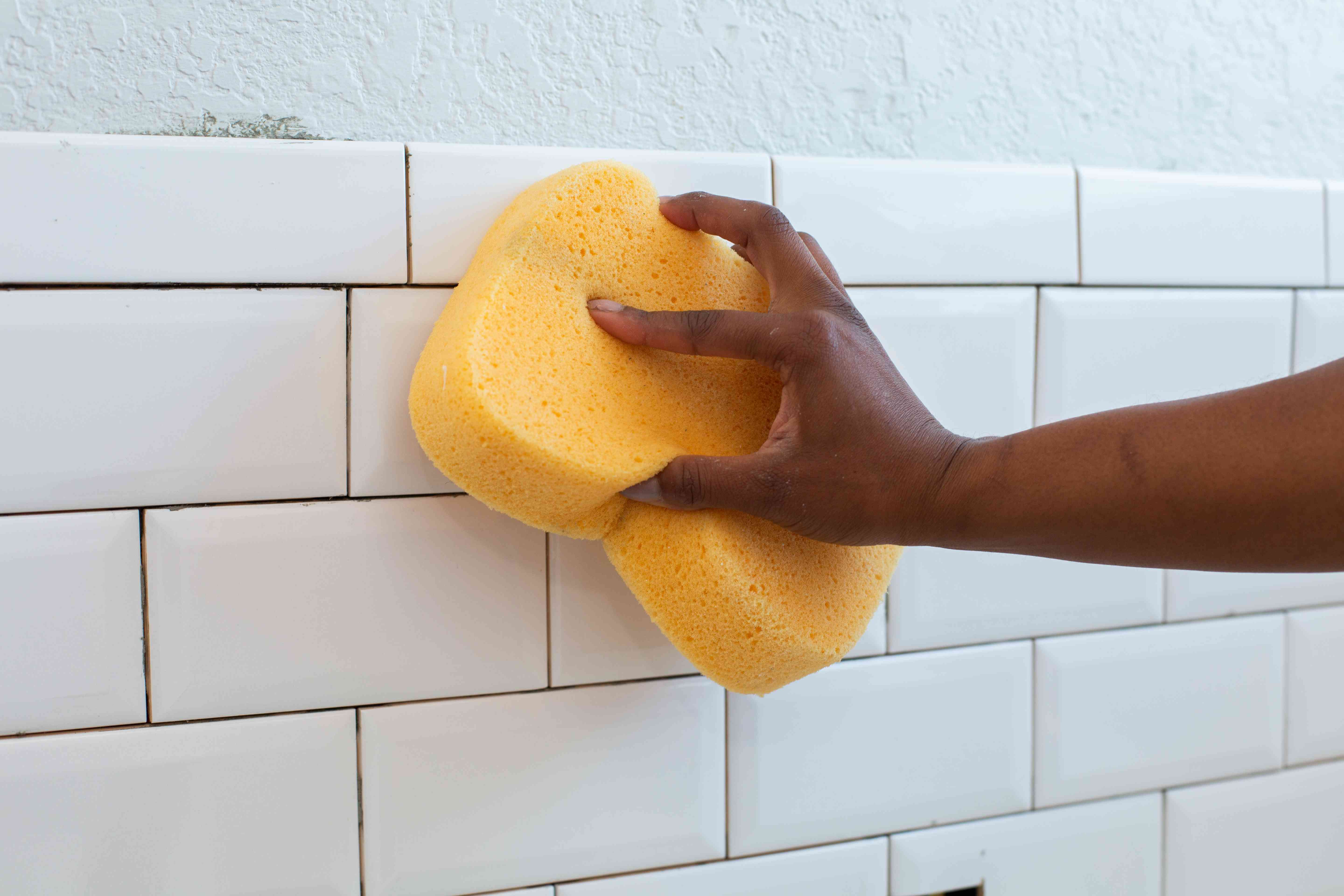 White ceramic tile cleaned with yellow sponge before applying grout