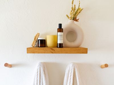 Small wooden bathroom shelf with items on top and wooden pegs with towels hanging