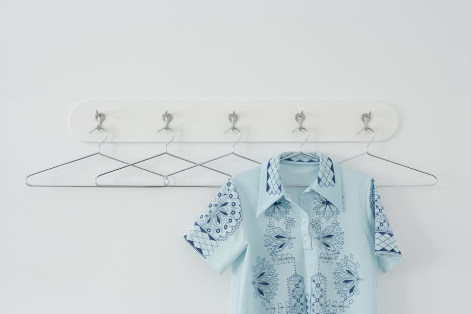 Shirt hanging amongst empty hangers on row of hooks