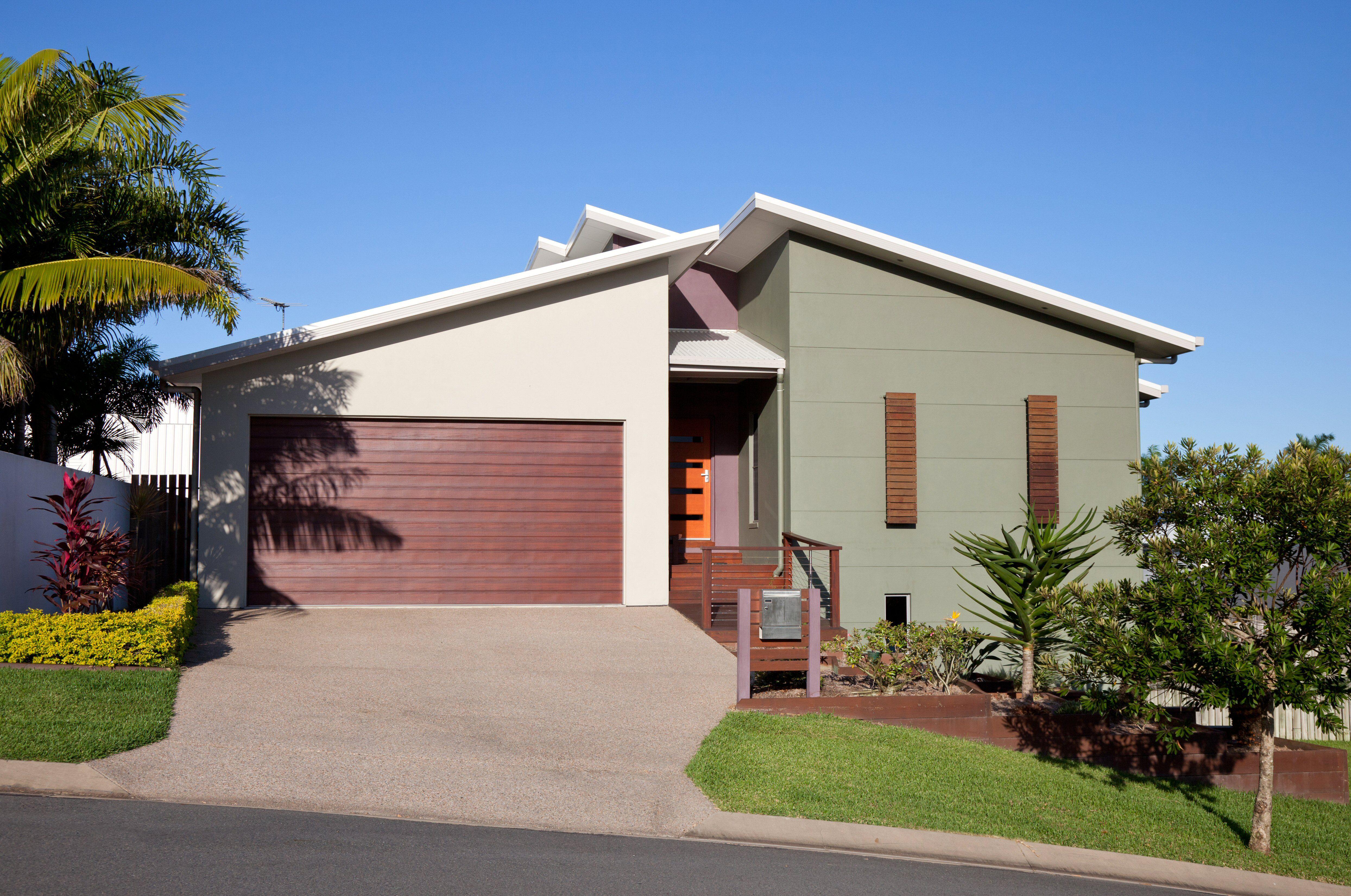 casa moderna de estuco de color verde musgo con largas ventanas de persianas rojizas con garaje inclinado para dos autos con techo inclinado de un color más claro pero puerta del mismo color rojizo
