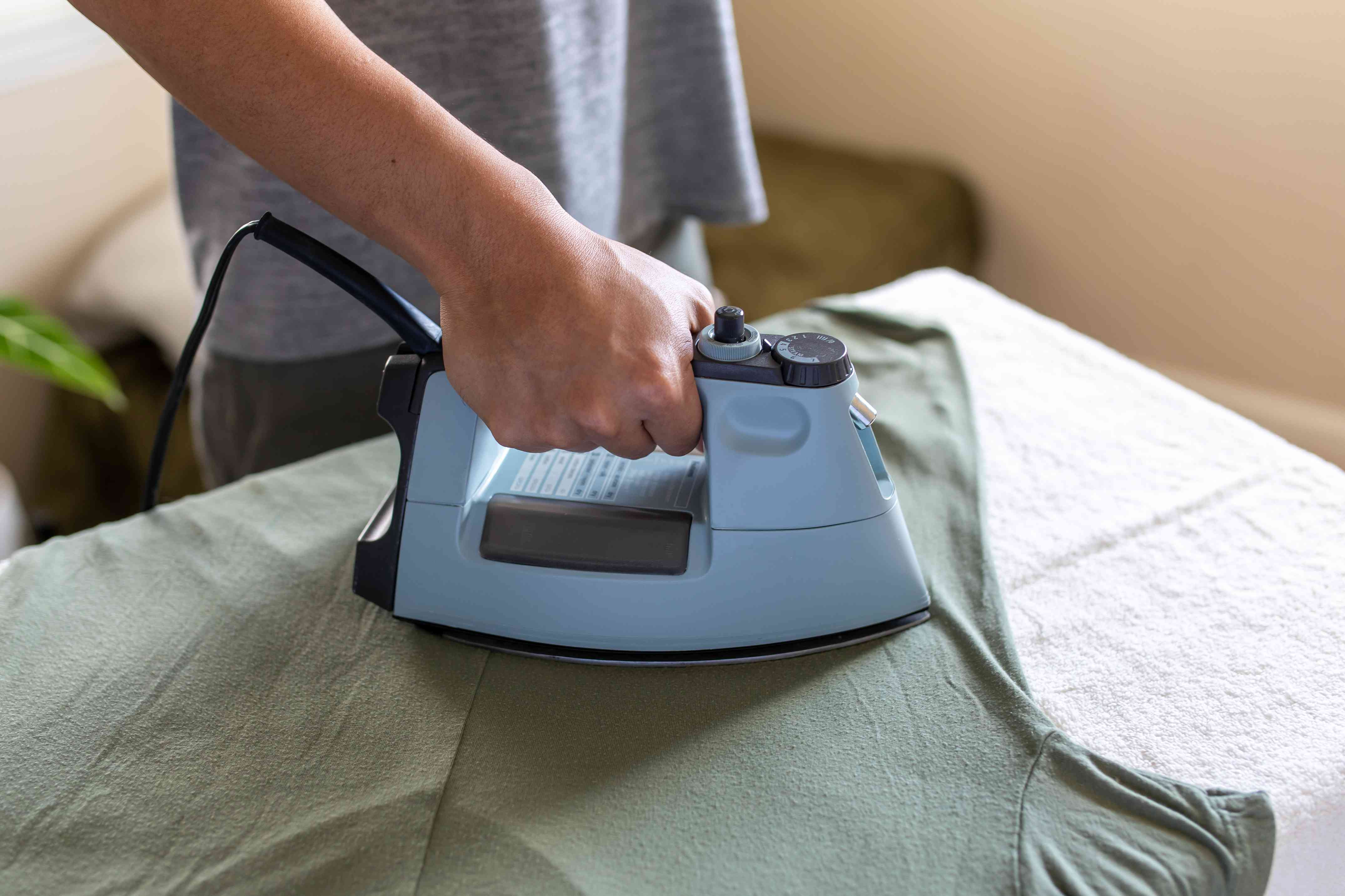 person ironing over a white towel