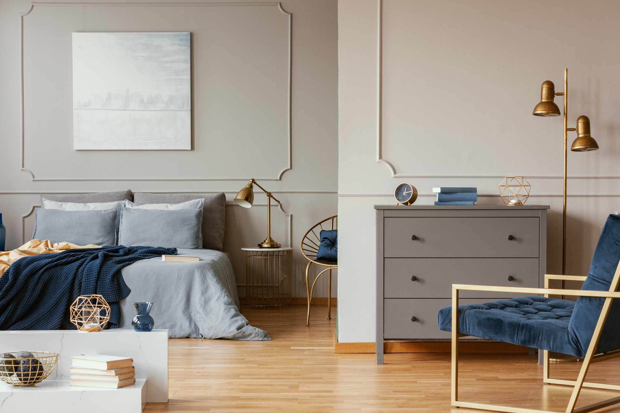 Pastel blue abstract painting above king size bed in elegant bedroom with gold accents