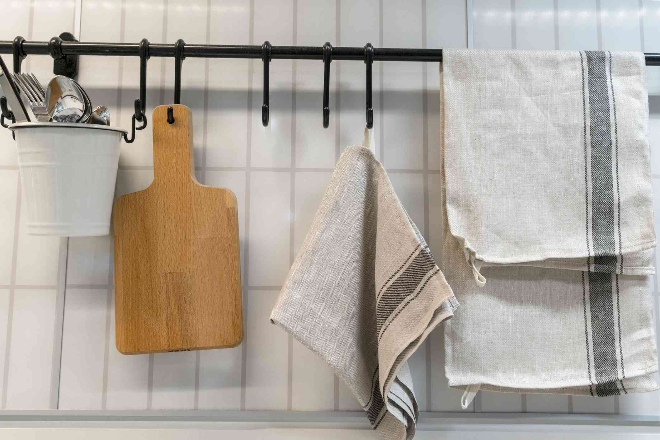 A kitchen towel and utensils are hanging on the wall. scandinavian cuisine