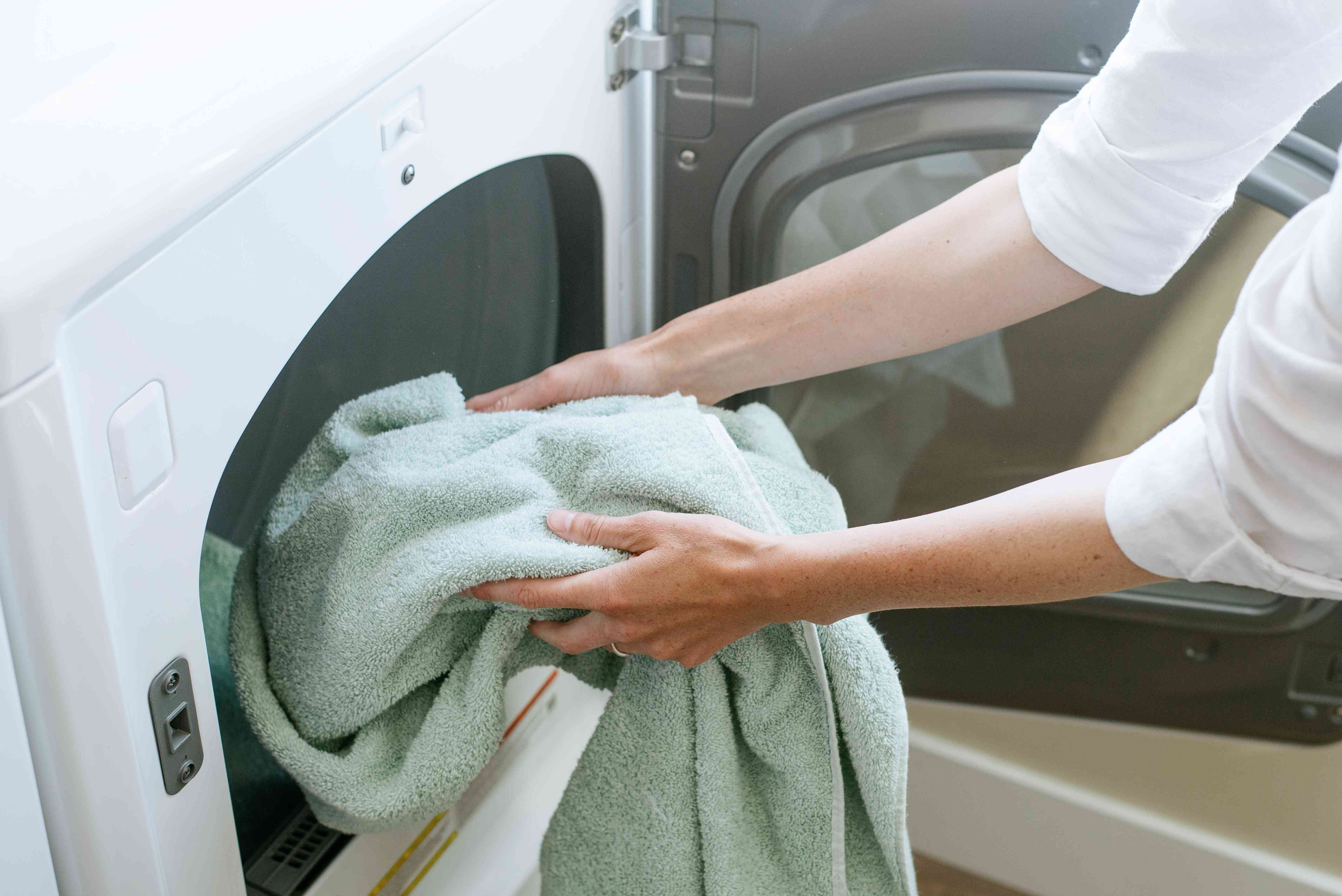 Mint green towel being placed in drying machine