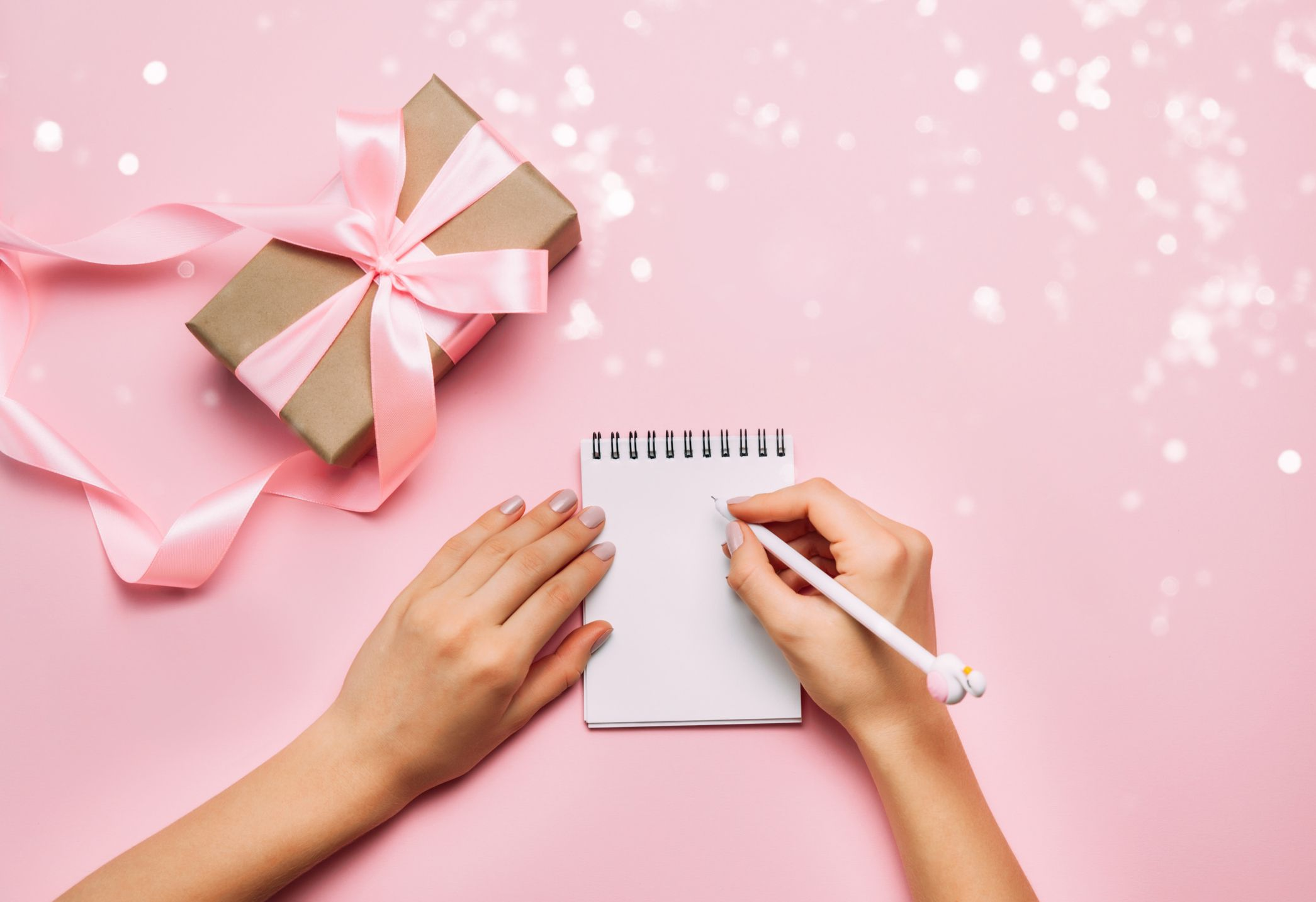 Hand writing in notebook with party gift