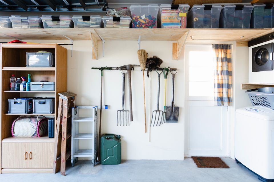 Garage organized with plastic boxes on wooden shelves and rakes held on the wall