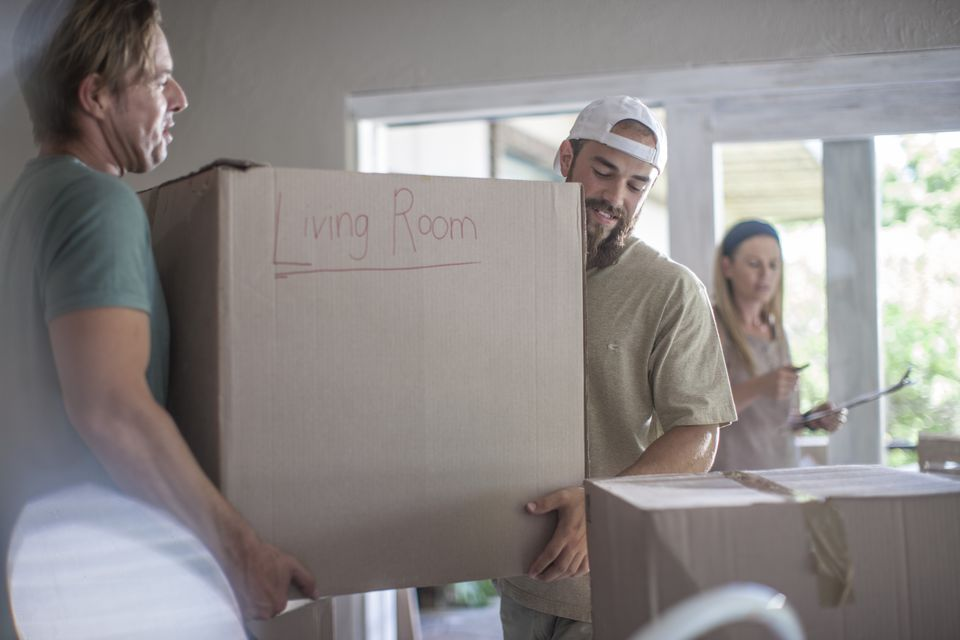Two men carrying a cardboard box that reads: Living Room while a woman stands in the background.