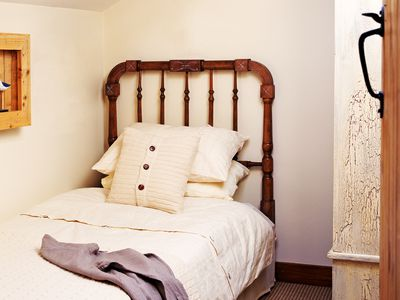 a single bed with a wooden headboard with one side against the wall