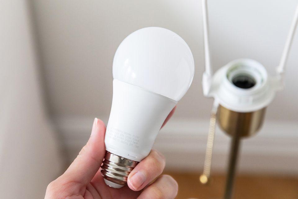 Light bulb held in hand in front of empty light fixture