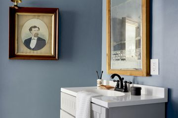 Blue bathroom mirror and sink with wall art