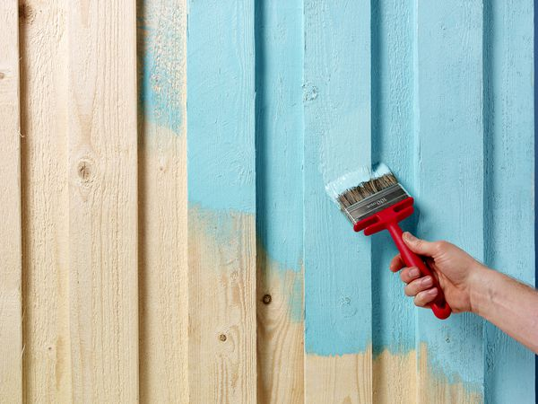 Hand and paintbrush painting a fence