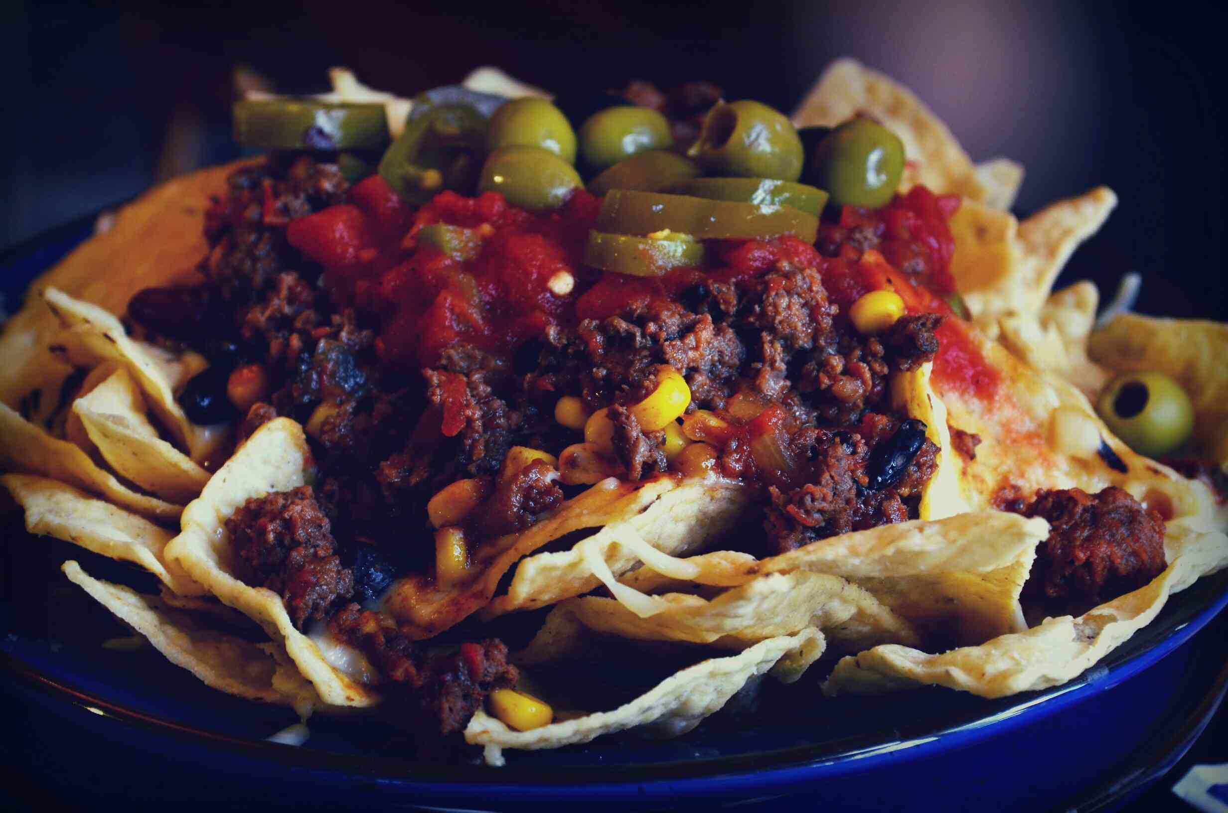 Nachos with meat, olives, peppers, and tomatoes.